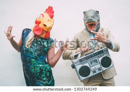 Crazy senior couple wearing chicken and t-rex mask while dancing outdoor - Mature trendy people having fun celebrating and listening music with boombox - Absurd concept of masquerade funny holidays
