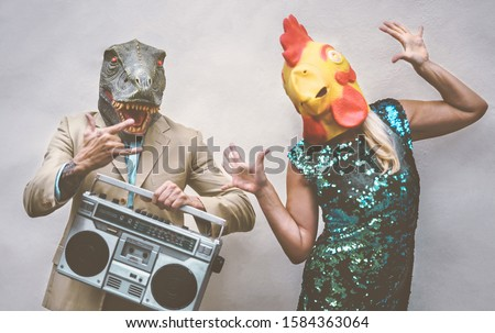 Crazy senior couple wearing chicken and t-rex mask while dancing outdoor - Mature trendy people having fun celebrating and listening music with boombox - Absurd concept of masquerade funny holidays Foto stock ©