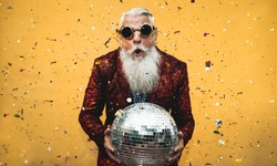 Crazy senior man having fun doing party during holidays time - Elderly people celebrating life concept