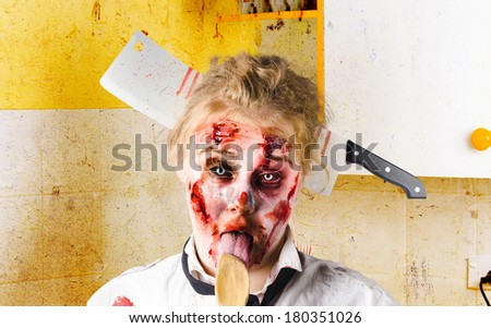 Crazy sick monster cook licking wooden spoon inside yellow kitchen with meat cleaver through head. GMO food