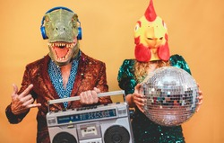 Crazy stylish people listening music with vintage boombox stereo - Fashion couple wearing t-rex and chicken mask at party fest event -  Absurd, holidays and funny trend concept - Focus on man face