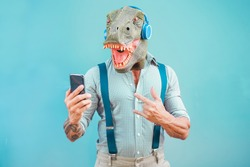Crazy tattooed man with t-rex mask using smartphone while listening music - Crazy senior male having fun with mobile phone app - Technology trends and fashion concept - Focus on face