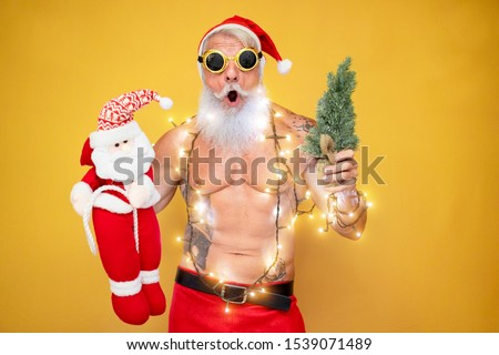 Crazy tattooed Santa Claus wearing vintage christmas lights - Fit senior man with winter holiday costume posing in front of the camera - Winter, trendy people, vacation concept - Focus on his face