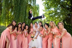 Crazy Wedding. Bride and bridesmaids having fun after wedding ceremony. Groom flying in background with help of groomsmen. Bridesmaid dresses. Bride groom and guests at wedding day. Wedding concept
