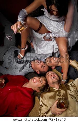 Crazy wedding party in night club. bride making a drunkard of friends of groom