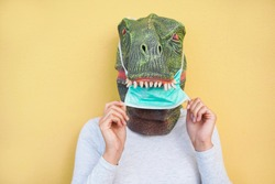 Crazy woman wearing t-rex and medical protection masks - Quarantine isolation lifestyle during coronavirus time - Absurd and funny trend concept - Focus on nose