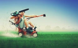 Crazy workman covered with instruments driving lawn mower over green grass