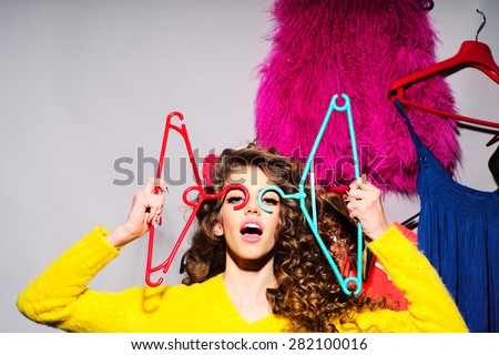 Crazy young girl with curly hair in yellow sweater holding hangers standing amid colorful clothes pink red blue colors on grey wall background, horizontal picture