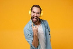 Crazy young man in blue shirt posing isolated on yellow orange background. People lifestyle concept. Mock up copy space. Listen music with headphones, showing horns up gesture, heavy metal rock sign