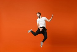 Crazy young man in casual white t-shirt posing isolated on orange wall background studio portrait. People lifestyle concept. Mock up copy space. Having fun, jumping fooling around like playing guitar