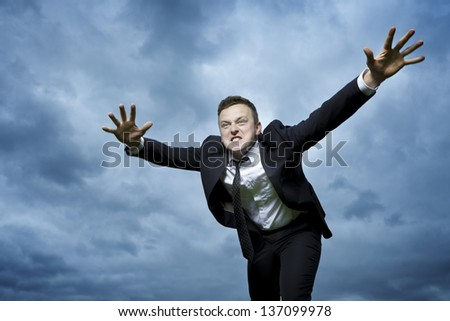 Crazy young man throws himself in front of him to attack. I want to catch something. He is furious and determined to reach your goal.