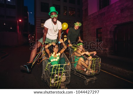Crazy young men and women having fun with shopping trolleys at night on city street. Friends having fun on St.Patrick's day celebration on street.
