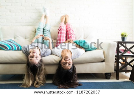 Crazy young women having fun while lying upside down on sofa at home #1187202037