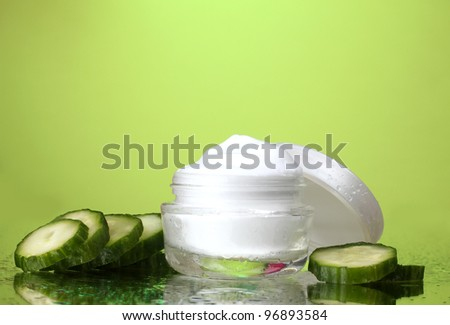 cream and fresh sliced cucumber on green background