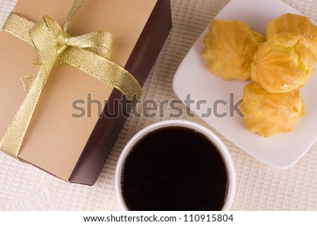 Cream cake with coffee and gift. Sweet Profiterole, Coffee and Present on the Table