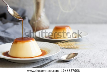 Cream caramel pudding with caramel sauce in plate on white rustic table Stock photo ©