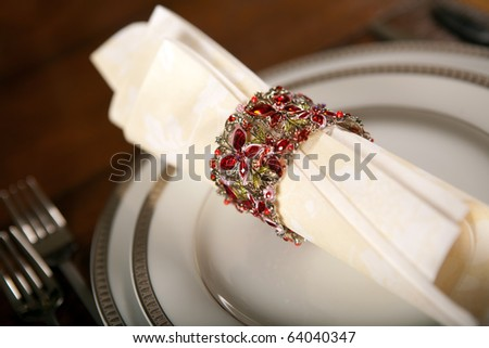 Cream colored festive napkin with ornate fancy napkin ring on a holiday table