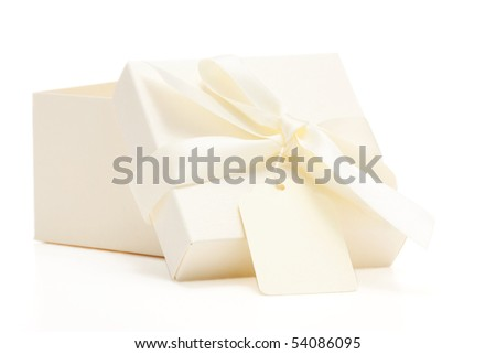 cream colored gift box with attached bow and name tag; white background