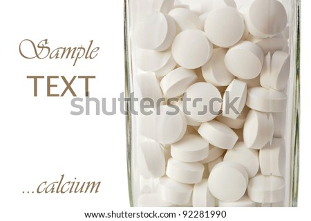 Cream colored nutritional supplements (calcium with magnesium and vitamin d) in glass bottle on white background with copy space.