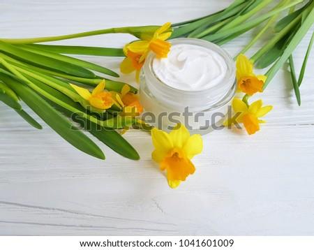 cream cosmetic daffodil on white wooden handmade