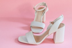 cream female sandals on a pink paper background, closeup side view.