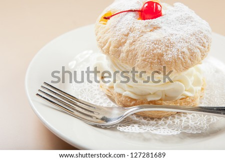 Cream filled puff pastry with cherry on top.