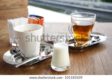 Cream for coffee or tea with a cup of coffee and a cup of tea with tissue paper and sugar on the wood table