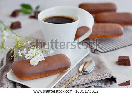 Cream long john donuts filled with cream and strawberry glaze and dipped in chocolate. Served with a black coffee.  ストックフォト ©