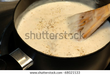 Cream of Mushroom soup in saucepan cooking on stove and stirred with slotted wooden spoon.