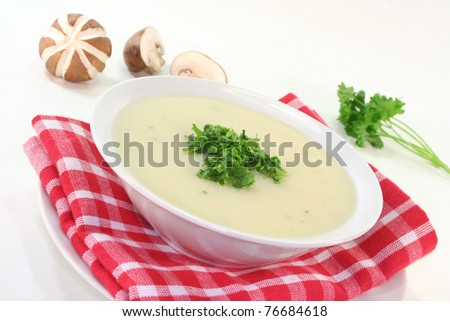 Cream of mushroom soup with fresh mushrooms, bread and parsley