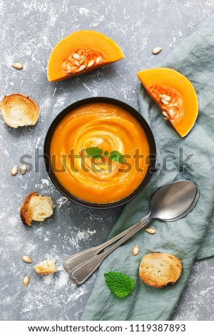 Cream of pumpkin soup served with toasted bread on a gray background. View from above, flat lay.