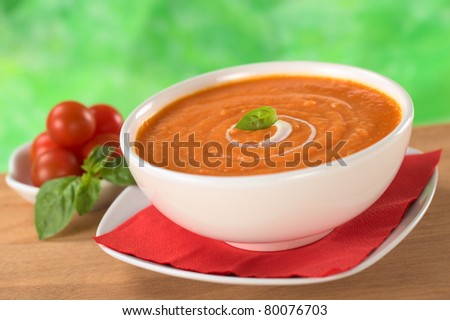 Cream of tomato with a small spiral of cream on top and a basil leaf with tomatoes and basil leaves in the back (Selective Focus, Focus on the basil leaf in the bowl)