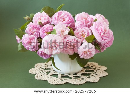 Cream roses bunch in vase on green background. Still life with roses bouquet