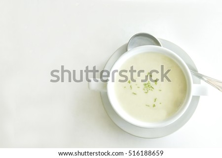 Cream soup in white cup on white table background with space for text here #516188659