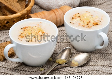 cream soup of cauliflower with cheese and pepper in a cups, close-up
