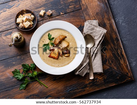 Cream-soup with porcini mushroom with croutons on wooden table