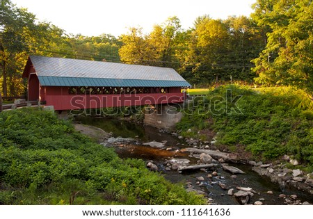 Creamery covered bridge built in 1879 in Brattleboro Vermont. Beautiful historic red covered bridge with a flowing stream of water below it.