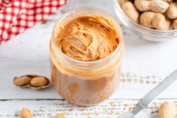 Creamy and smooth crunchy peanut butter in jar on white wood table. Natural nutrition and organic food.