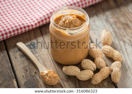 Creamy and smooth peanut butter in jar on wood table. Natural nutrition and organic food. Selective focus. #316086323