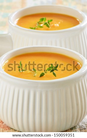 Creamy carrot and sweet potato soup with sprig of thyme in white ...