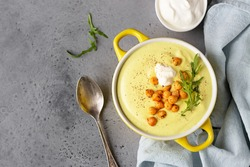 Creamy cauliflower curry soup with roasted chickpea, sour cream and arugula in a bowl on grey stone background. Top view.