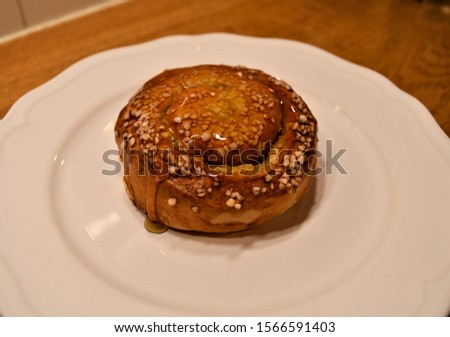 creamy cinnamon bun with granulated sugar on a white plate
