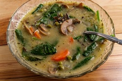 Creamy mushroom and wild rice soup with spinach carrots and green peas