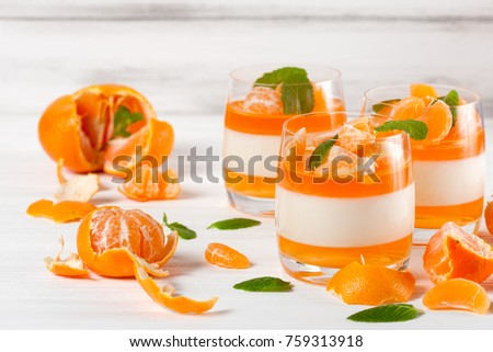 Creamy panna cotta with orange jelly in beautiful glasses and fresh ripe mandarin on white wooden background. Closeup photography of delicious dessert.