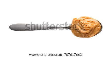 Creamy peanut butter in spoon on white background #707617663