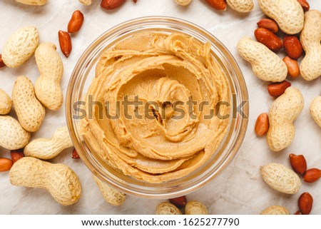 Creamy peanut paste, peanut butter in open glass jar in the center of peanuts food background. Peanuts in shell, peeled peanuts on white background . Vegan food concept. Creamy peanut paste flat lay.