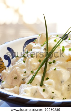Creamy potato salad garnished with chives.