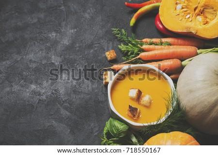 Shutterstock Creamy pumpkins soup with vegetables over black texture. selective focus. copy space