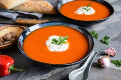 Creamy roasted red bell pepper soup with sour cream in a ceramic plate