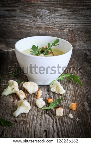 creamy soup from a cauliflower with toasts  on a wooden background